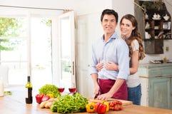 Pares jovenes felices que trabajan en cocina Foto de archivo
