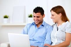 Pares jovenes felices que trabajan en la computadora portátil Imagen de archivo