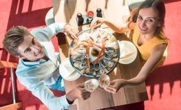 Pares jovenes felices que tuestan durante cena romántica en un restaurante de moda Foto de archivo