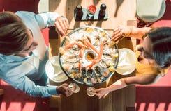 Pares jovenes felices que tuestan durante cena romántica en un restaurante de moda Imagenes de archivo