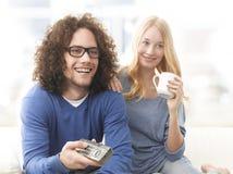 Pares jovenes felices que ven la TV Fotografía de archivo libre de regalías