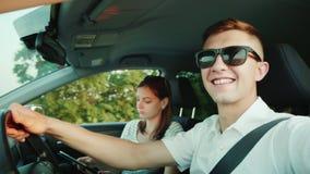 Pares jovenes felices que viajan en el coche, hombre que hace el selfie, mirando la cámara, sonriendo feliz junto almacen de video
