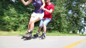 Pares jovenes felices rollerblading en un día soleado maravilloso en el parque, sosteniéndose la cintura almacen de video