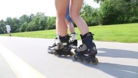 Pares jovenes felices rollerblading en un día soleado maravilloso en parque, vista de piernas almacen de video
