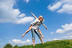 Pares jovenes felices - saltando en el cielo Foto de archivo libre de regalías