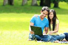 Pares jovenes felices usando el ordenador portátil al aire libre Fotos de archivo