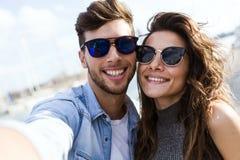 Pares jovenes felices usando el teléfono móvil en la calle Fotografía de archivo libre de regalías