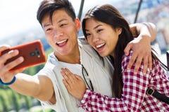 Pares jovenes felices usando el teléfono móvil en la ciudad Fotos de archivo