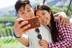 Pares jovenes felices usando el teléfono móvil en la ciudad Imagen de archivo libre de regalías