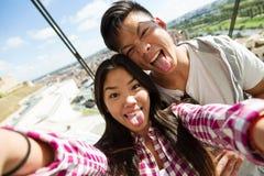 Pares jovenes felices usando el teléfono móvil en la ciudad Imagen de archivo