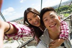Pares jovenes felices usando el teléfono móvil en la ciudad Fotos de archivo libres de regalías