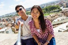 Pares jovenes felices usando el teléfono móvil en la ciudad Fotografía de archivo