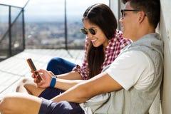 Pares jovenes felices usando el teléfono móvil en la ciudad Imágenes de archivo libres de regalías
