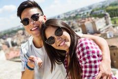 Pares jovenes felices usando el teléfono móvil en la ciudad Imagenes de archivo