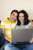 Pares jovenes felices usando la computadora portátil Imágenes de archivo libres de regalías
