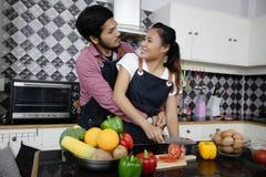 Pares jovenes felices y sonrientes que cocinan la comida en la cocina en ho fotos de archivo libres de regalías
