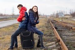 Pares jovenes fríos que se sientan esperando un tren Imagenes de archivo