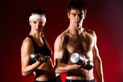 Pares jovenes fuertes que se resuelven con pesas de gimnasia Fotos de archivo