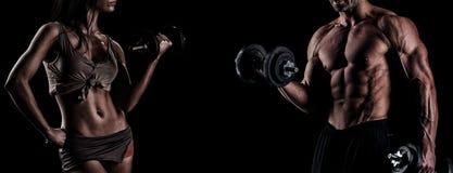 Pares jovenes fuertes que se resuelven con pesas de gimnasia Tirado en el estudio o imagenes de archivo