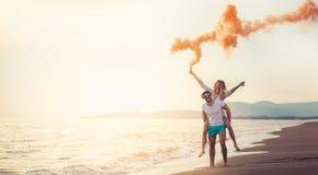 Pares jovenes hermosos con la bomba de humo en la playa fotos de archivo libres de regalías