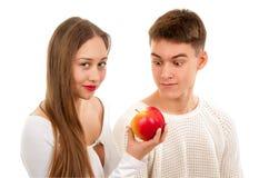 Pares jovenes hermosos con la manzana fotos de archivo
