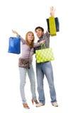 Pares jovenes hermosos con los bolsos de compras Foto de archivo libre de regalías