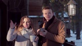 Pares jovenes hermosos de la tarjeta del día de San Valentín del día feliz del ` s con té caliente en la cabaña almacen de video