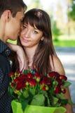 Pares jovenes hermosos de los amantes del retrato con un ramo de ROS rojo Imágenes de archivo libres de regalías