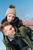 Pares jovenes hermosos en amor en el parque en un día de invierno soleado claro La muchacha se sienta en la parte de atrás de su  fotos de archivo