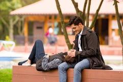 Pares jovenes hermosos en amor en día de tarjetas del día de San Valentín del st, mujer reclinada en sus piernas del novio, en pa Imagenes de archivo