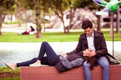 Pares jovenes hermosos en amor en día de tarjetas del día de San Valentín del st, mujer reclinada en sus piernas del novio, en pa Fotografía de archivo