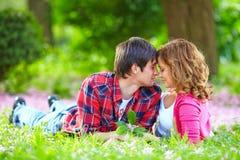 Pares jovenes hermosos en amor en hierba de la primavera Fotos de archivo libres de regalías