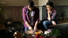 Pares jovenes hermosos en cocina en casa mientras que cocina la comida sana El hombre es ensalada de los cortes La mujer se sient almacen de metraje de vídeo