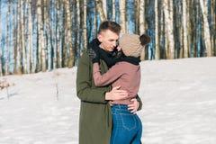 Pares jovenes hermosos en el amor que abraza en el parque en un día de invierno soleado claro foto de archivo libre de regalías