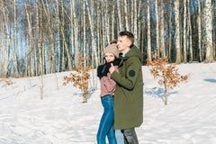 Pares jovenes hermosos en el amor que abraza en el parque en un día de invierno soleado claro imagenes de archivo