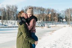 Pares jovenes hermosos en el amor que abraza en el parque en un día de invierno soleado claro Abrazos del muchacho y besar a su n fotografía de archivo