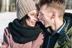 Pares jovenes hermosos en el amor que abraza en el parque en un día de invierno soleado claro imágenes de archivo libres de regalías