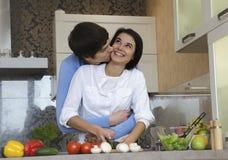 Pares jovenes hermosos en la cocina Imagen de archivo
