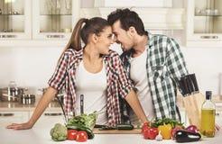 Pares jovenes hermosos en la cocina mientras que cocina foto de archivo libre de regalías
