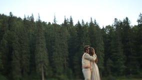 Pares jovenes hermosos en la ropa ucraniana tradicional que abraza en el bosque en Cárpatos metrajes