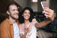 Pares jovenes hermosos que hacen las fotos en cámara frontal del teléfono móvil en restaurante Fabricación afroamericana bonita d fotos de archivo libres de regalías