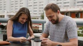 Pares jovenes hermosos que juegan al juego en línea en sus smartphones La muchacha pierde, los triunfos 4K del individuo almacen de video