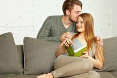 Pares jovenes hermosos que leen un libro en el sofá Imagen de archivo