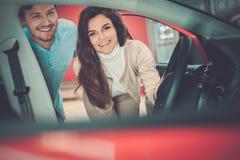 Pares jovenes hermosos que miran un nuevo coche la sala de exposición de la representación Fotos de archivo libres de regalías