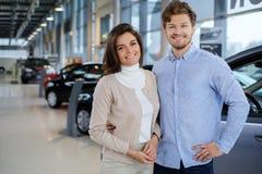 Pares jovenes hermosos que miran un nuevo coche la sala de exposición de la representación Foto de archivo libre de regalías
