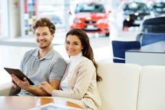 Pares jovenes hermosos que miran un nuevo coche la sala de exposición de la representación Imagen de archivo libre de regalías