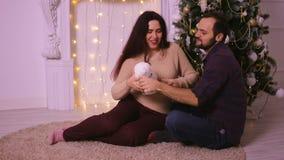 Pares jovenes hermosos que ríen y que se divierten en la Navidad El sentarse en la alfombra beige delante de la chimenea metrajes