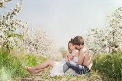 Pares jovenes hermosos que se besan en el GA floreciente Imagenes de archivo