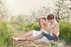 Pares jovenes hermosos que se besan en el GA floreciente Foto de archivo