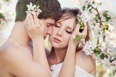 Pares jovenes hermosos que se besan en el GA floreciente Imagen de archivo libre de regalías